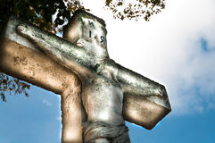 Jesus Christ. Crucifixion Jesus Christ statue on the sky background and natural light. Public sculpture in the cemetery Stock Photos