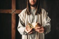 Jesus Christ dà il pane ad alimento fedele e sacro immagine stock