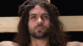 Jesus Christ de grito na coroa de espinhos que olham a câmera, crucificação na cruz vídeos de arquivo
