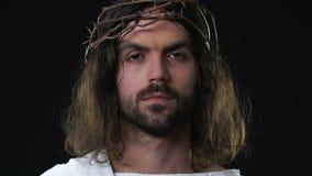 Jesus Christ de grito na coroa se espinhos que olham a câmera contra o fundo escuro filme