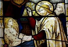 Jesus Christ, der ein krankes Mädchen im Buntglas heilt stockbild