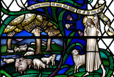 Jesus Christ der gute Hirte mit Schafen im Buntglas Stockfotografie