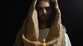 Jesus Christ en el traje que lleva a cabo la vela ardiendo contra el fondo oscuro, luz almacen de metraje de vídeo