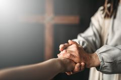 Jesus Christ gives a helping hand to the faithful. Jesus Christ in white robe gives a helping hand to the faithful, crucifixion cross on background. Son of God Stock Photography
