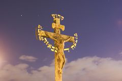 Jesus Christ on gold cross. Golden sculpture of Jesus Christ on cross with starry sky and cloudscape background Royalty Free Stock Photo