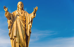 Jesus Christ golden statue over blue sky. Old Jesus Christ golden statue over blue sky stock photography