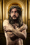 Jesus Christ with a halo of golden light in a chapel. Jesus Christ calvary, man bleeding, representation of passion with crown of thorns art Stock Images