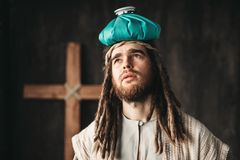 Jesus Christ with a heating pad on his head. Man in the image of Jesus Christ with a heating pad on his head, crucifixion cross on black background Royalty Free Stock Photos