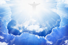 Jesus Christ in heaven. Jesus Christ in blue sky with clouds, bright light from heaven, resurrection, easter stock image