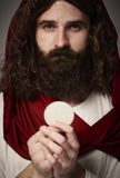 Jesus Christ. Holding holy Eucharist in hands stock photography
