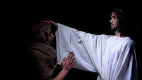 Jesus Christ i krona av taggar som välsignar den fattiga mannen i ämbetsdräkt, förälskelse och vänlighet royaltyfri foto