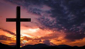 Jesus Christ kreuzen, hölzernes Kruzifix auf einem himmlischen Hintergrund mit drastischem Licht und Wolken und bunter orange Son stockfotografie