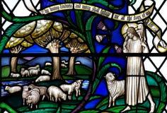 Jesus Christ le bon berger avec des moutons en verre souillé Photographie stock