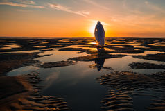 Jesus Christ Low Tide Pools. Image of Jesus Christ standing on a beach pools area at low with the sun going down Royalty Free Stock Photography
