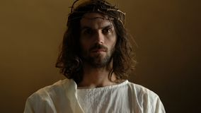 Jesus Christ na coroa de espinhos que guardam a vela de queimadura, símbolo da ressurreição vídeos de arquivo
