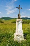 Jesus Christ on old wayside cross in meadow. Royalty Free Stock Photography