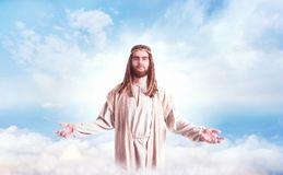 Jesus Christ with open arms against cloudy sky. Jesus Christ in white robe standing with open arms against cloudy sky. Son of God, christian faith Stock Image
