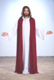 Jesus Christ with open arms. Personification of Jesus Christ standing with open arms, illuminated background royalty free stock image