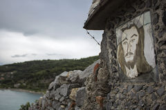 Jesus Christ painted on a stone& x27;s wall. Jesus face painting on a stone& x27;s wall close the cemetery in Portovenere, Italy Royalty Free Stock Photo