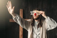 Jesus Christ in party glasses reaching out hand. Man in the image of Jesus Christ in party glasses reaching out his hand, crucifixion cross on black background Stock Image
