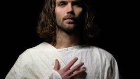 Jesus Christ pleurant dans la couronne des épines tenant la main près du coeur, gentillesse, foi banque de vidéos