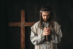 Jesus Christ praying with bible in hands. Man in the image of Jesus Christ praying with bible in hands, cross on black background. Prayer against crucifixion royalty free stock photos