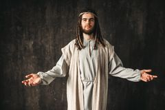 Jesus Christ praying with open arms. Jesus Christ in white robe praying with open arms, dark background. Son of God, christian faith Royalty Free Stock Photos