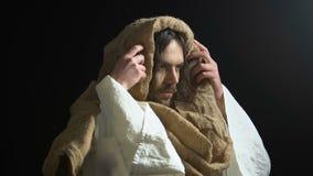 Jesus Christ que levanta as mãos para o céu, abençoando o deus para a mercê, fundo preto filme