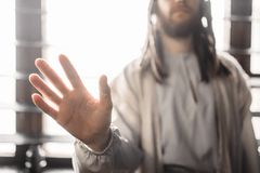 Jesus Christ reaching out his hand, peace symbol. Jesus Christ in white robe reaching out his hand, window with sunlight on background, peace symbol. Son of God Royalty Free Stock Images