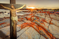 Jesus Christ Resurrection. Cross of Christ statue on a blood red cliff, with ocean background in a cloudy sunrise. From clouds the sun rays light the wooden Stock Image
