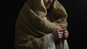 Jesus Christ in robe holding string of beads and praying to God, saving grace. Stock footage stock video