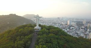Jesus Christ`s Statue in Vung Tau, Vietam, Asia, South-East Asia, 4k drone footage. Sunset and many buildings visible