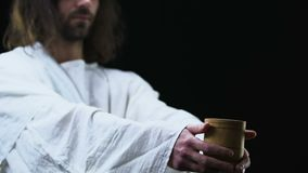 Jesus Christ showing cup of water to camera, helping poor people charity concept
