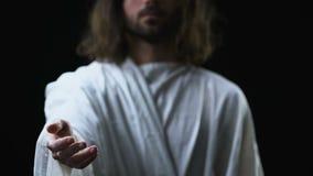 Jesus Christ som når hjälpande den ut handen som tar anda till himmel, svart bakgrund lager videofilmer