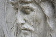 Jesus Christ statue against a background of gray stone (close up