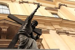 Jesus Christ statue with cross and pointing hand finger against cathedral building in Warsaw, Poland. Christian saint. Religious concept. Religious stone Stock Photos