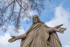 Jesus christ. Statue of Jesus Christ  with outstretched hands in front of blue sky with clouds Stock Images