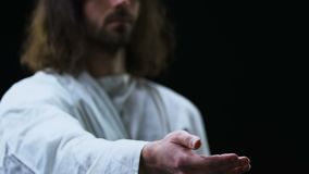 Jesus Christ stretching helping hand against black background, faith and belief. Stock footage stock video