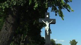 Jesus Christ sur la croix au cimetière sous un arbre de tilleul, près de l'église de pèlerinage banque de vidéos