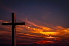 Jesus Christ träkors på en bakgrund med dramatisk färgrik solnedgång och apelsinen, purpurfärgad himmel Royaltyfri Bild