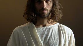 Jesus Christ-verpersoonlijking in kroon van doornen tegen donkere achtergrond, geloof stock footage