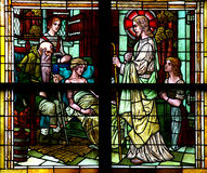 Jesus Christ visiting a sick person in stained glass. Stained glass window of Jesus Christ visisting a sick person stock photos