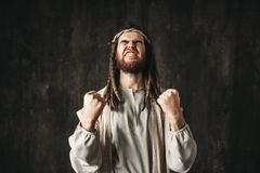 Jesus Christ in white robe emotionally pray. S clenching hands into fists, dark background. Son of God, strong faith in God Royalty Free Stock Image