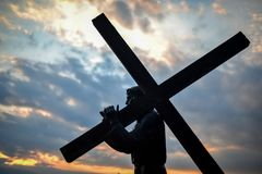 Jesus Christ with the wood cross in the evening royalty free stock image