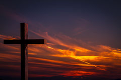 Jesus Christ wooden cross on a background with dramatic, colorful sunset, and orange, purple sky. Jesus Christ cross. Christian wooden cross on a background with Royalty Free Stock Image