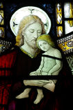 Jesus Christ with a young child in his arms (in stained glass) Royalty Free Stock Photos