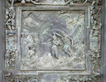 Jesus Christs Baptism. Sculpture work from Giambologna school, collocated in the left portal panel of the Cathedral St. Mary of the Assumption in Pisa, Italy Stock Photo