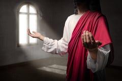 Jesus-Christus hief handen met open palmen en het bidden aan god binnen de ruimte op stock fotografie