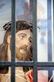 Jesus Christushauptstatue hinter Stäben Stockfotografie