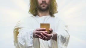 Jesus clemente que alcança para fora as mãos com o vidro de madeira que dá a água fresca aos povos video estoque